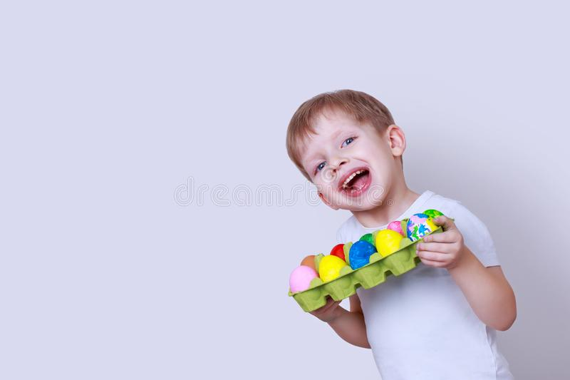 Boy with painted eggs. Little boy smiles and holds in his hands a cardboard box with painted eggs royalty free stock image