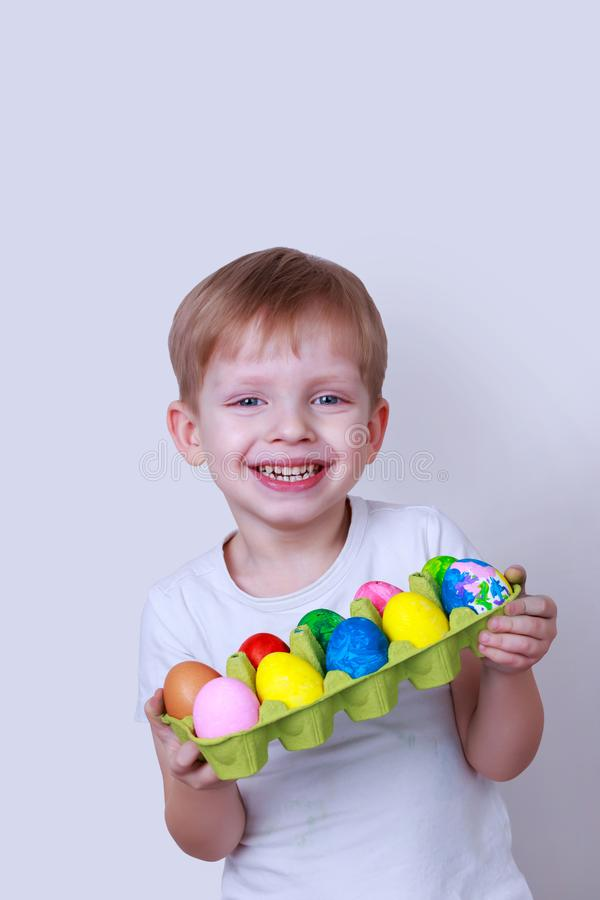 Boy with painted eggs. Little boy smiles and holds in his hands a cardboard box with painted eggs stock images