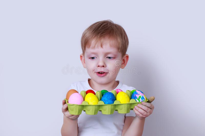 Boy with painted eggs. Little boy smiles and holds in his hands a cardboard box with painted eggs royalty free stock images