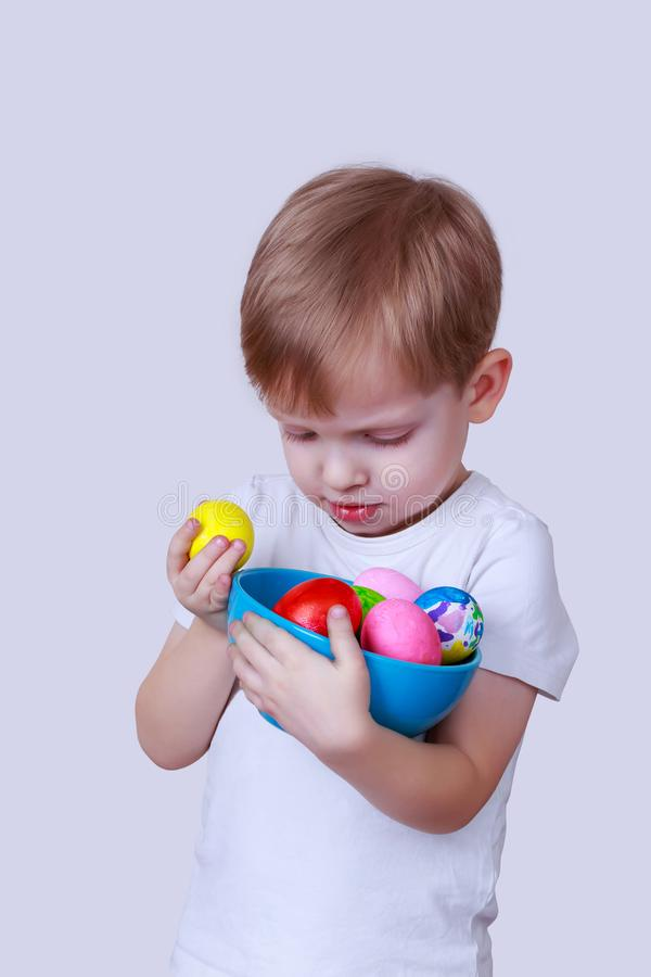 Boy with painted eggs. Little boy smiles and holds in his hands a plate with painted eggs royalty free stock photography