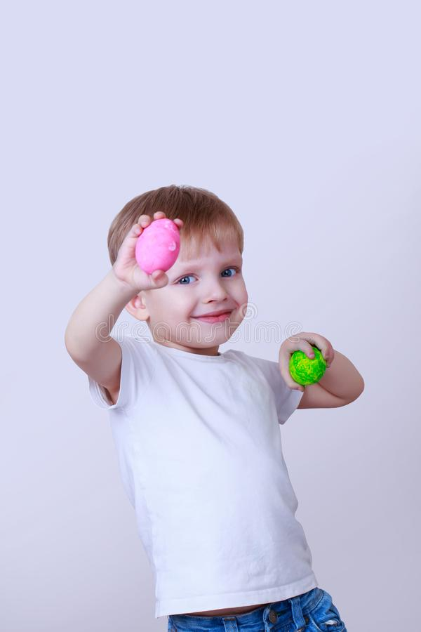 Boy with painted eggs. The little boy smiles and holds two painted eggs on a beige background stock images