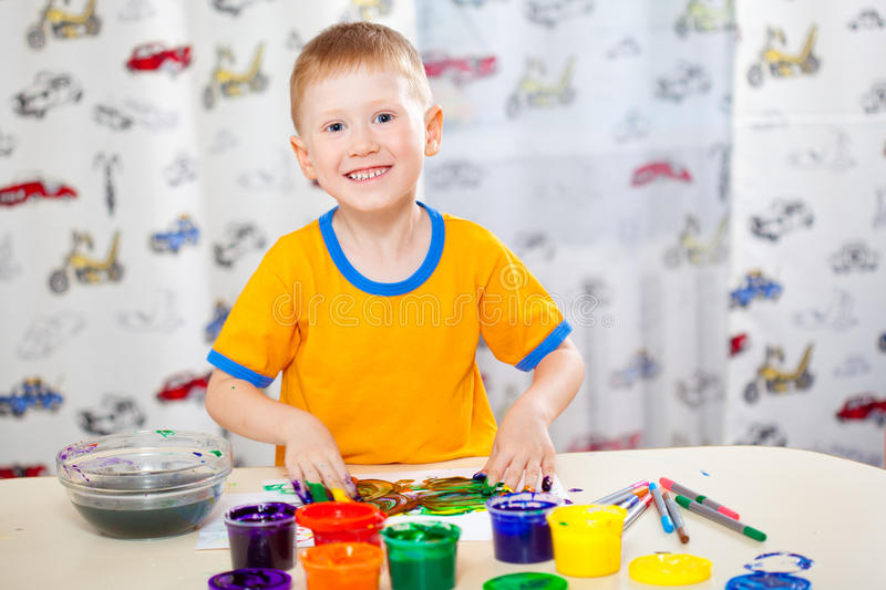 Boy with painted fingers. Funny boy with painted fingers, painting at home stock photo