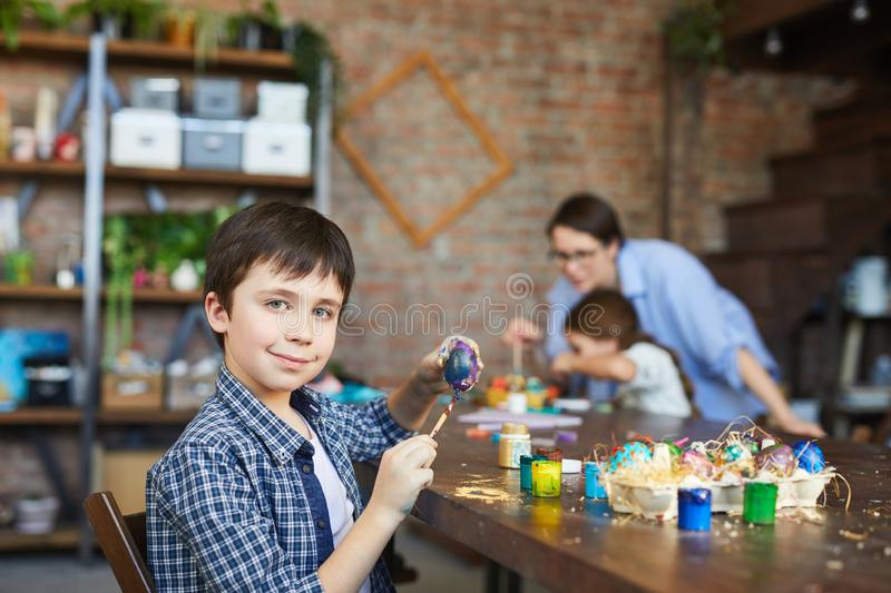 Boy Painting Easter Eggs. Portrait of smiling boy looking at camera while painting eggs for Easter in art studio, copy space stock image