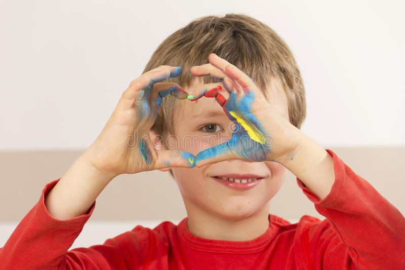 Boy is painting with finger paint stock photos