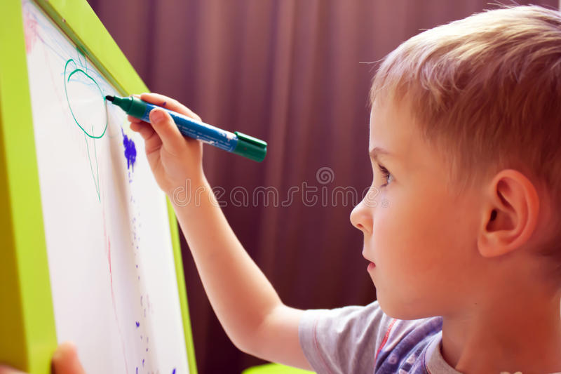 Boy paints on an easel stock photography