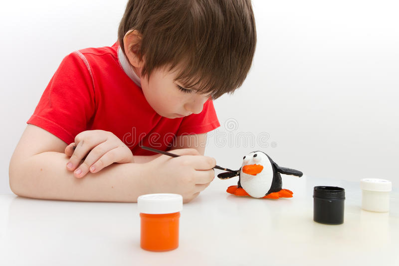 Boy paints a penguin made of salty dough stock photography