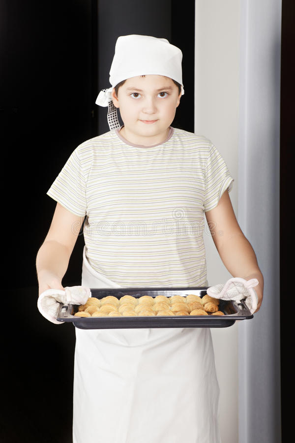 Boy with pan of croissants stock image