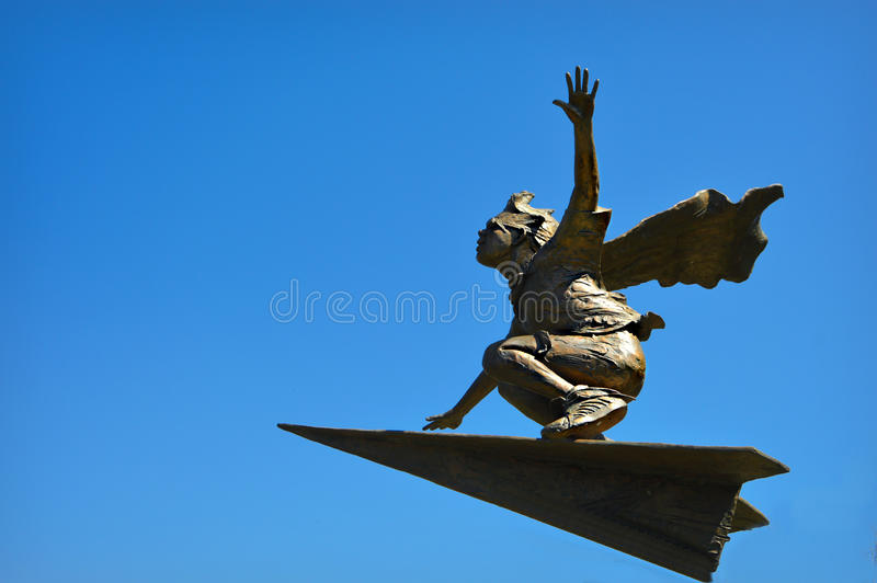 Boy Paper Airplane. A statue of a boy riding on top of a paper airplane through the sky with a cape that is flying in the wind as he balances himself on top of stock photo