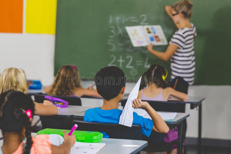Boy with a paper plane while teacher teaching in classroom stock photos