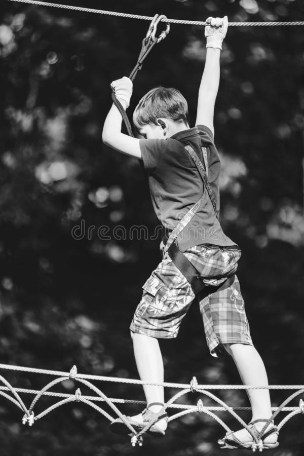 Boy passing cable route in extreme adventure park, BW shot stock images