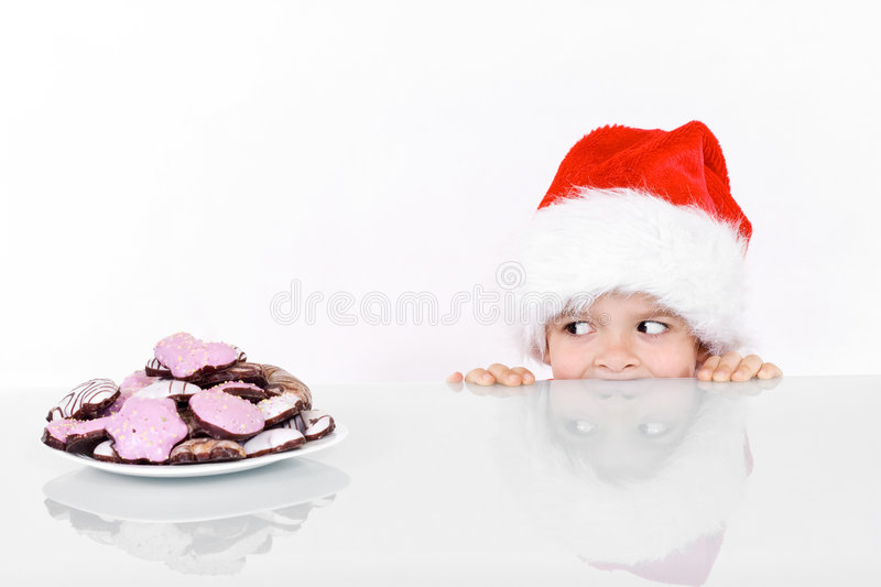 Boy peeking at the christmas gingerbread cookies. Isolated with reflections royalty free stock images