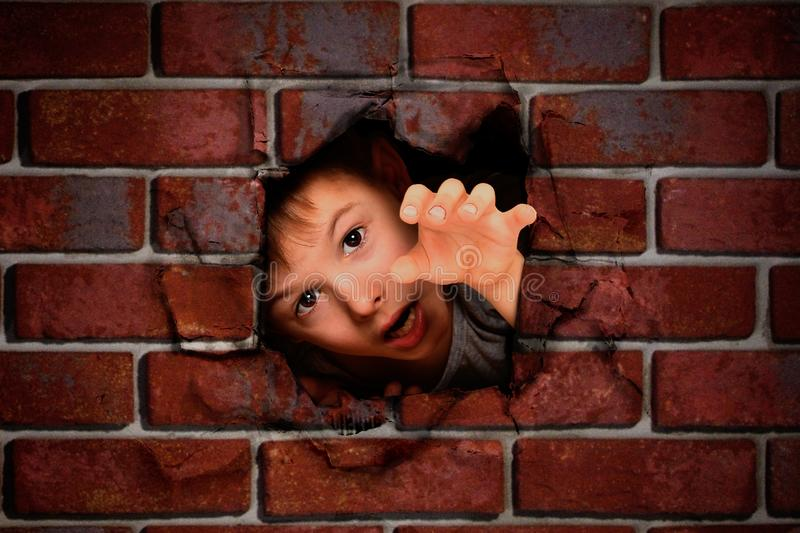 Boy peeking out of a hole in a brick wall stock images