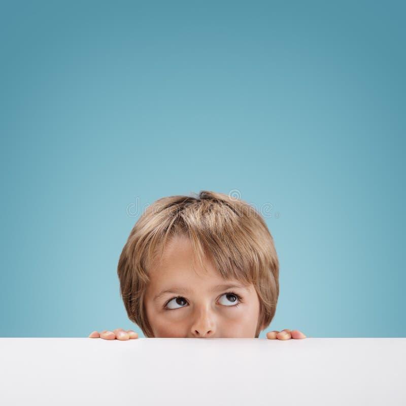 Boy peeking over a white board. Young boy peeking over a white board looking up at copy space for a message stock photos