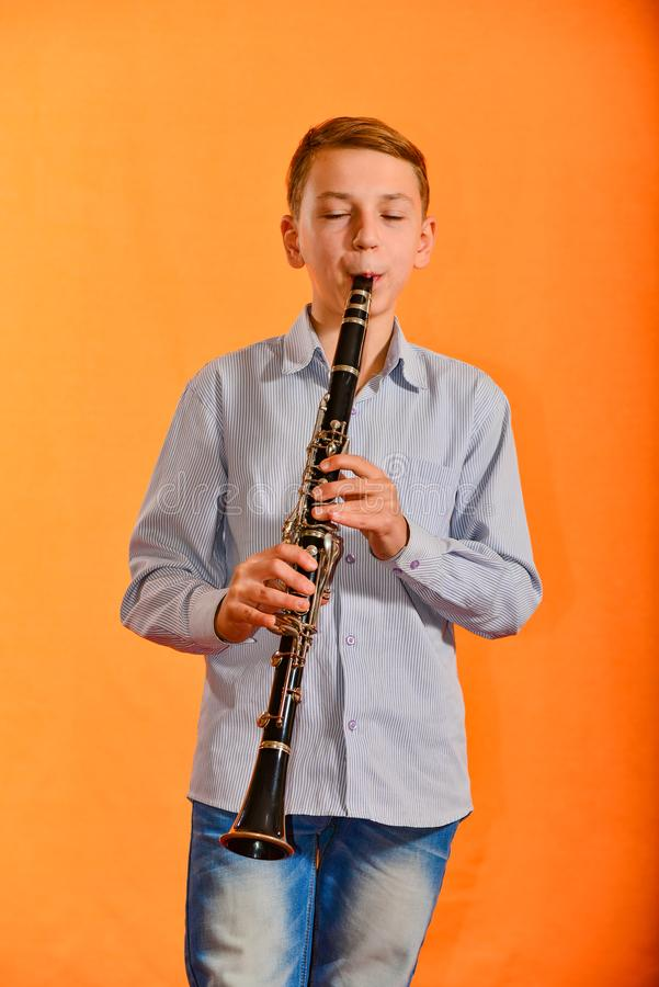 The boy performs solo at a concert, plays the clarinet on an orange background royalty free stock photos