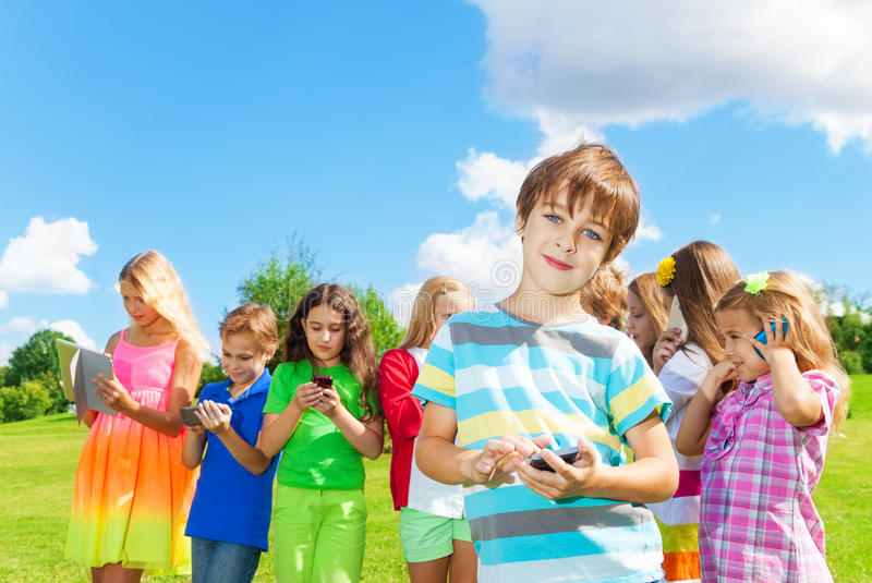 Boy with phone sms. One smiling school age boy standing with digital devices, text, sms, play, post to social network outside, with group of happy friends kids royalty free stock photos