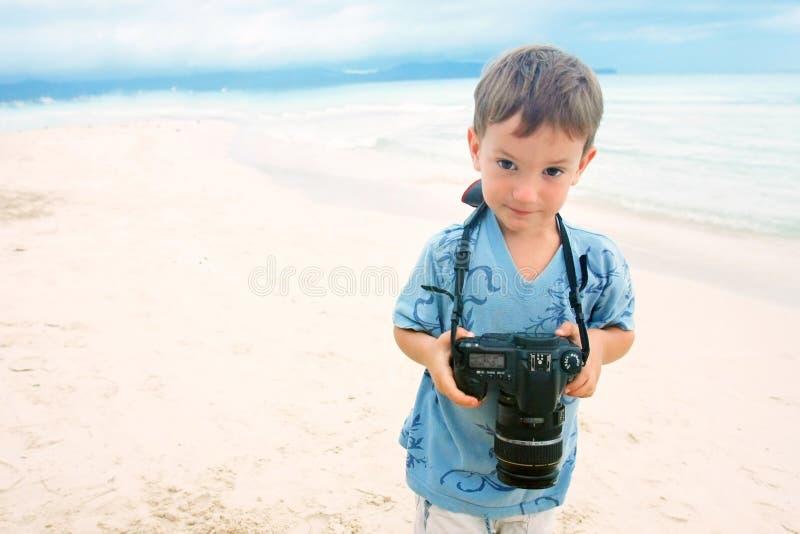 Boy with photo camera on beach background stock image