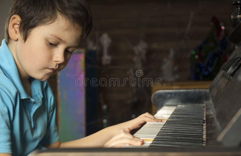 Boy at the piano stock photos