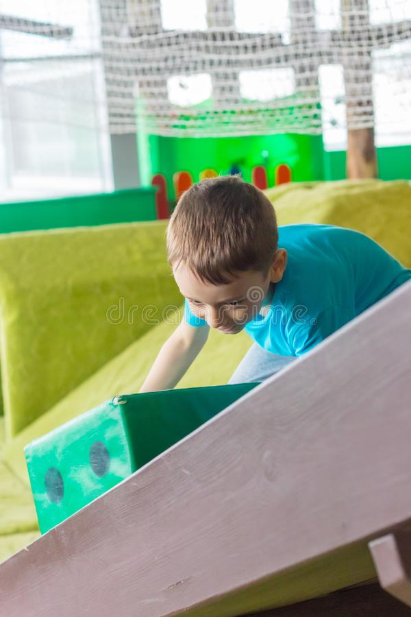 Boy picks up big dice on hill. Active games. stock photo