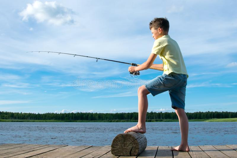 The boy on the pier, on a background of blue sky and lake, catches a fish on a bait stock photo