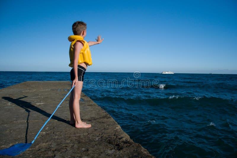 Boy on the pier waving stock image