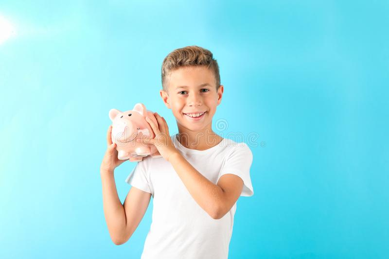 Boy with piggy bank against color background. Space for text stock photos