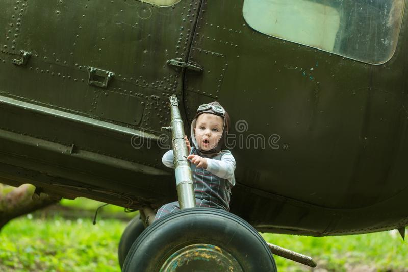 Boy in pilot helmet with glasses on green grass stock images