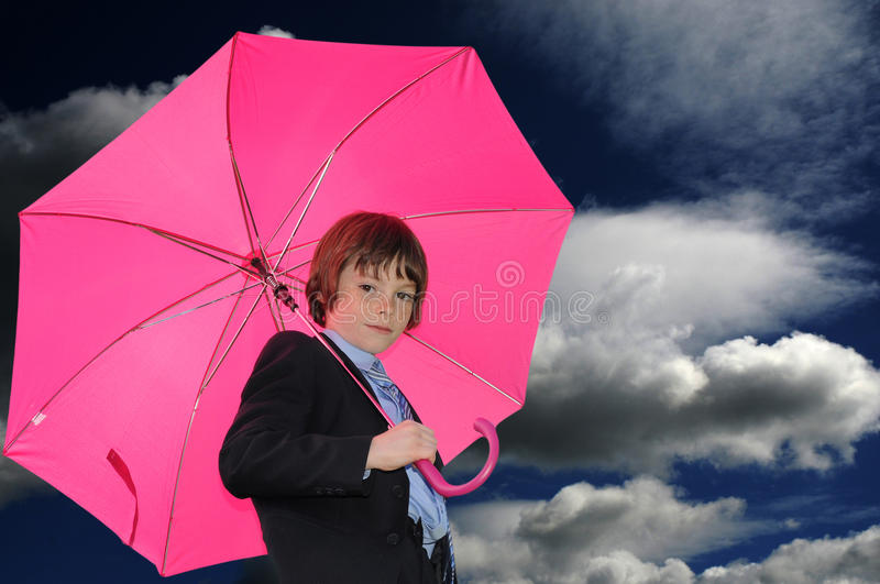 Boy with pink umbrella. In front of a cloudy sky stock photos