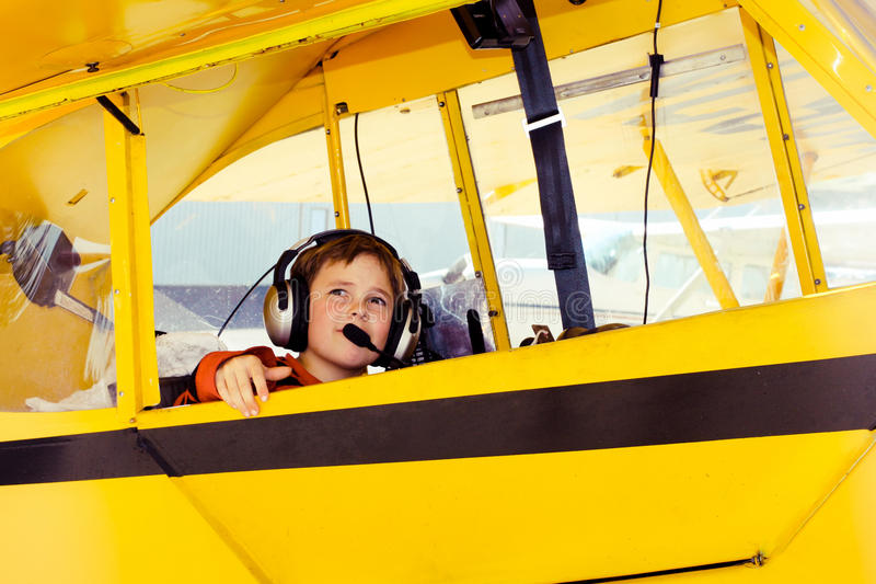 Boy in Piper Cub airplane wearing headset. A little nine-year-old boy looks out of the window of a 1946 yellow Piper Cub airplane. He wears a headset and a red stock photo