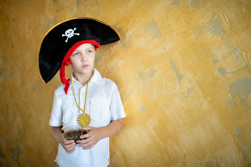 Boy pirate black hat. Boy pirate preparing for the holiday Halloween. Big pirate hat captain of a ship, male role play at a costume party children`s holiday. Fun royalty free stock photography