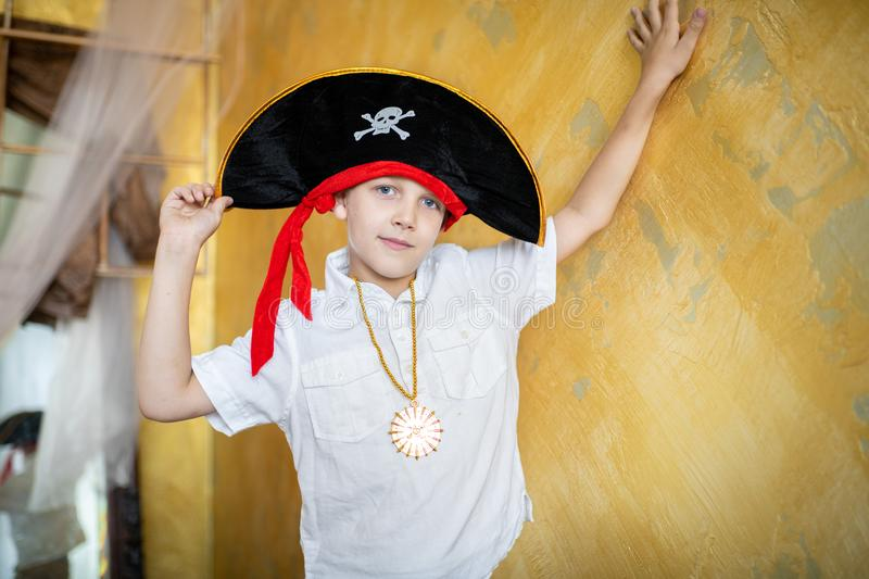 Boy pirate black hat. Boy pirate preparing for the holiday Halloween. Big pirate hat captain of a ship, male role play at a costume party children`s holiday. Fun royalty free stock photo