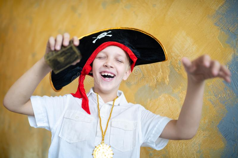 Boy pirate black hat. Boy pirate preparing for the holiday Halloween. Big pirate hat captain of a ship, male role play at a costume party children`s holiday. Fun stock photography