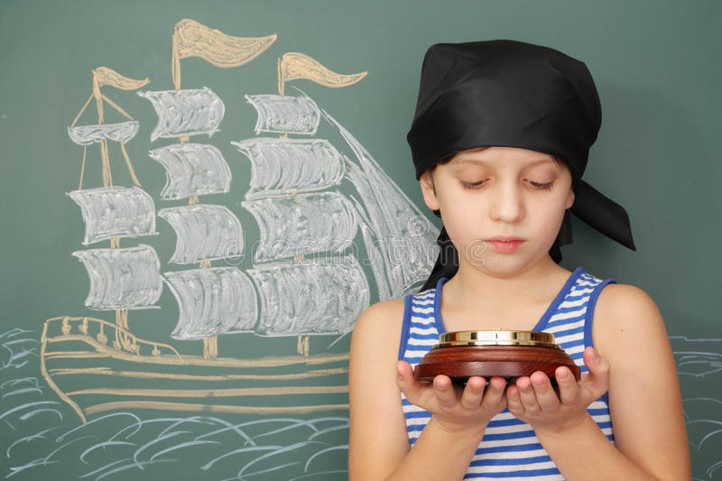 Boy pirate with compass. On background of ship stock images
