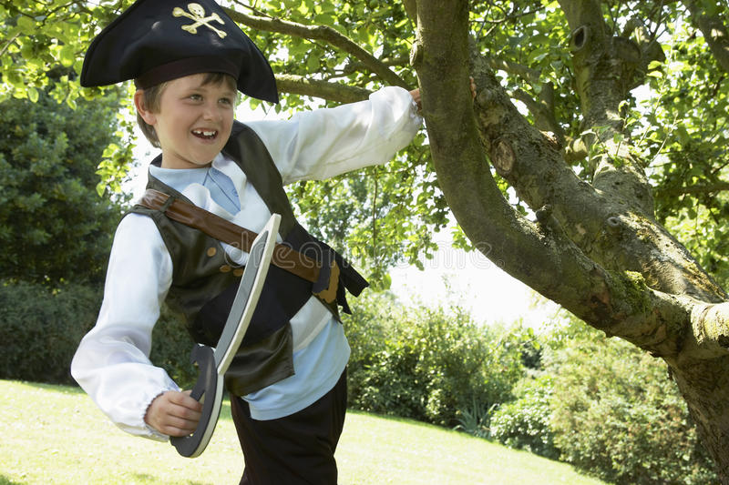 Boy In Pirate Costume Swinging From Tree royalty free stock photography