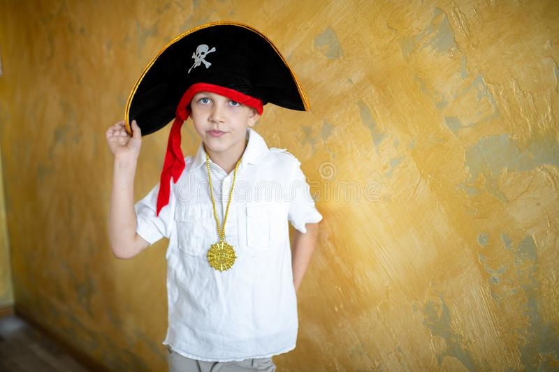 Boy pirate black hat. Boy pirate preparing for the holiday Halloween. Big pirate hat captain of a ship, male role play at a costume party children`s holiday. Fun stock image