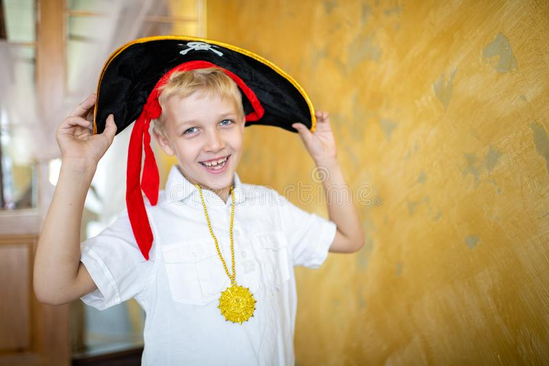 Boy pirate black hat. Boy pirate preparing for the holiday Halloween. Big pirate hat captain of a ship, male role play at a costume party children`s holiday. Fun royalty free stock photos