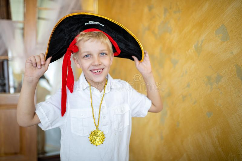 Boy pirate black hat. Boy pirate preparing for the holiday Halloween. Big pirate hat captain of a ship, male role play at a costume party children`s holiday. Fun stock images