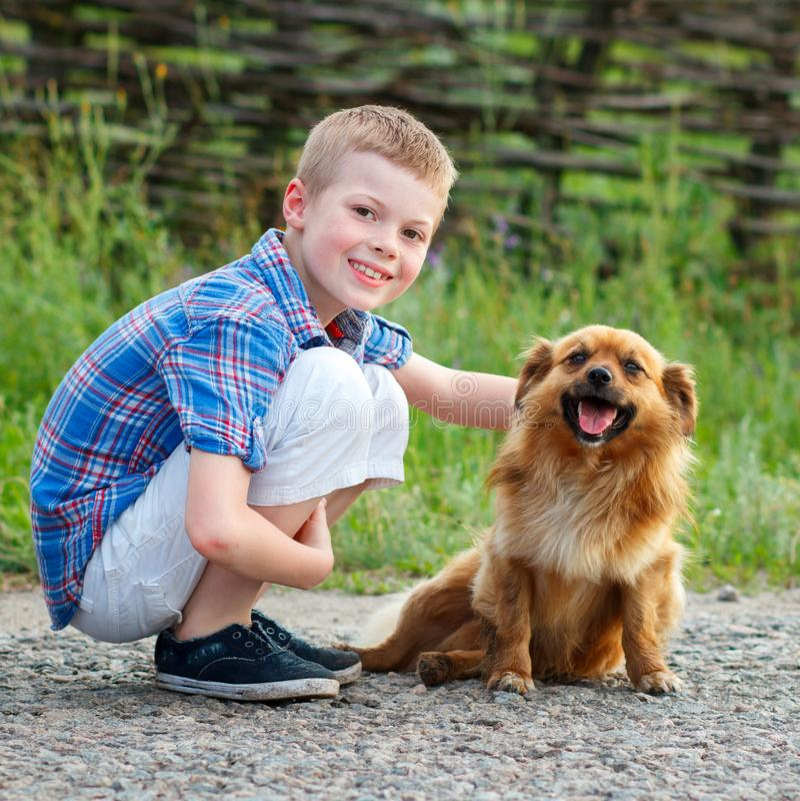 Boy in a plaid shirt hugging a red fluffy dog. Best friends. Ou stock photos