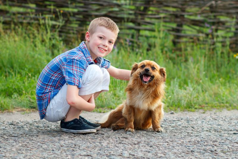 Boy in a plaid shirt hugging a red fluffy dog. Best friends. Outdoor royalty free stock images