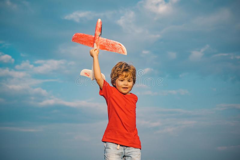 Boy with plane on meadow. Summer at countryside. Success and child leader concept. Childhood dream imagination concept. Kid pilot having fun on meadow. Active royalty free stock photos