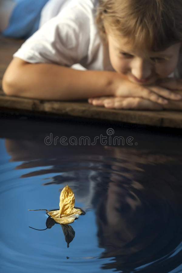 Boy play with autumn leaf ship in water, chidren in park play wi royalty free stock images