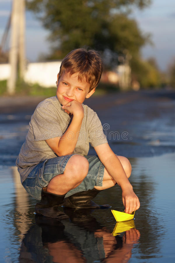 Boy play with autumn paper ship in water, chidren in park play w royalty free stock photo
