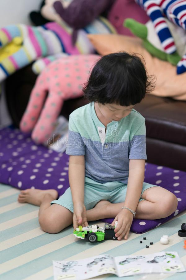 Boy play bricks for car on floor. Asian boy play bricks for making car on floor in room with dolls win blur background royalty free stock photos