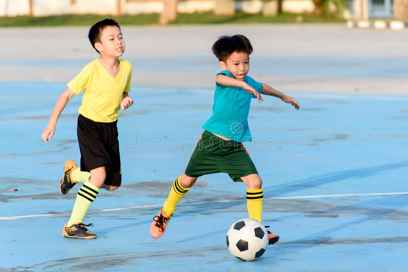 Boy play football on the blue concrete floor. Young Asian boy play football on the blue concrete floor during summer royalty free stock image