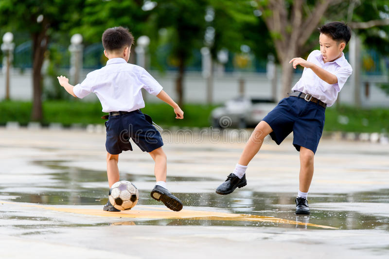 Boy play football. Boys in Thai student uniform black shoe play football on the concrete floor after the rainfall with the reflection stock photos