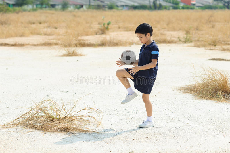 Boy play football on the dry soil ground. In a shiny day stock photography