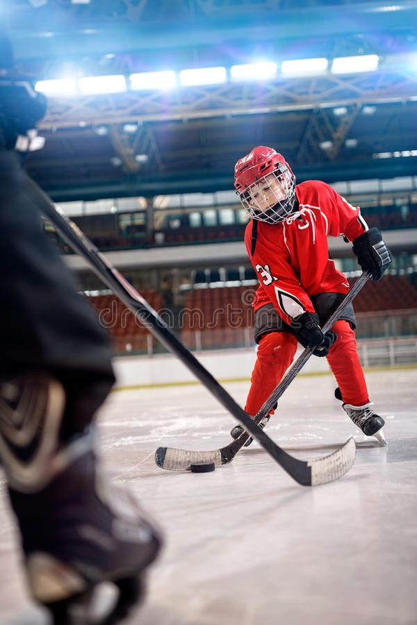 Boy play ice hockey in action kicking on goal. Young boy play ice hockey in action kicking on goal royalty free stock photos