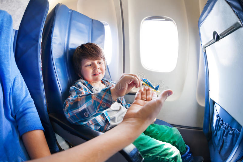 Boy play with mother in jet plane seat. Little boy takes little plane from moms hand sitting by the window in jet airplane royalty free stock images