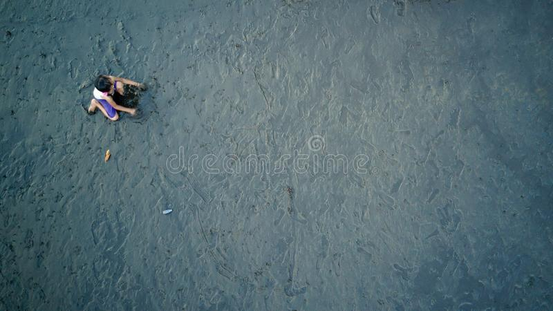 Boy play on sand with Dark shadow. Black sand and little wave on the beach in Indonesia royalty free stock photography