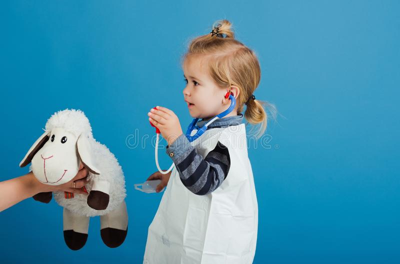 Boy play veterinarian with toy sheep in mothers hand. Child doctor examine toy pet with stethoscope on blue background. Veterinary clinic game. Future royalty free stock image