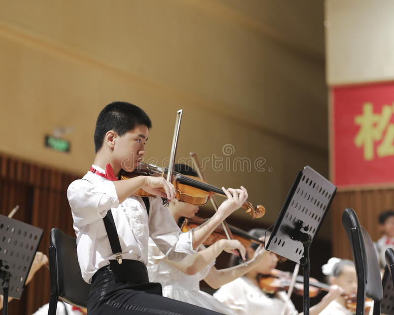 A boy play the violin carefully stock images